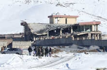 Afghan men stand in front of a collapsed building of a military base after a car bomb attack in Maidan Wardak, Afghanistan, Jan. 21, 2019.
