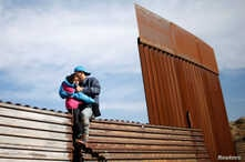 Migrants from Honduras, part of a caravan of thousands from Central America trying to reach the United States, jump onto a border fence to cross illegally from Mexico to the U.S., in Tijuana, Mexico, Dec. 12, 2018.