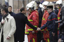 French President Emmanuel Macron (L) shakes hands with a firefighter during a visit in the streets of Paris on December 2, 2018, a day after clashes during a protest of Yellow vests against rising oil prices and living costs.