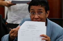 Maria Ressa, the award-winning head of a Philippine online news site Rappler that has aggressively covered President Rodrigo Duterte's policies, shows an arrest form after being arrested by National Bureau of Investigation agents in a libel case, Feb