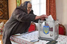 A local resident casts a vote into a mobile ballot box inside a house during a presidential election in the village of Zahiria in Lviv Region, Ukraine, March 31, 2019.