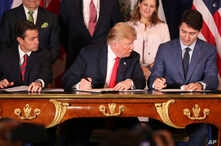 President Trump, looks over at Canada's Prime Minister Justin Trudeau's document as they and Mexico's President Enrique Pena Nieto sign a new United States-Mexico-Canada Agreement that replaces the NAFTA trade deal, at a hotel before the start of the...