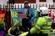 A supporter of WikiLeaks founder Julian Assange holds a placard in front of a police officer, as he stands outside Ecuador's embassy in London, April 6, 2019.