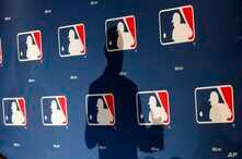 FILE - The shadow of MLB Commissioner Rob Manfred is projected on an MLB logo backdrop in Phoenix, Arizona, Feb. 23, 2015.