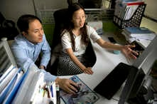 FILE - He Jiankui, left, and Zhou Xiaoqin work a computer at a laboratory in Shenzhen in southern China's Guangdong province, Oct. 10, 2018.