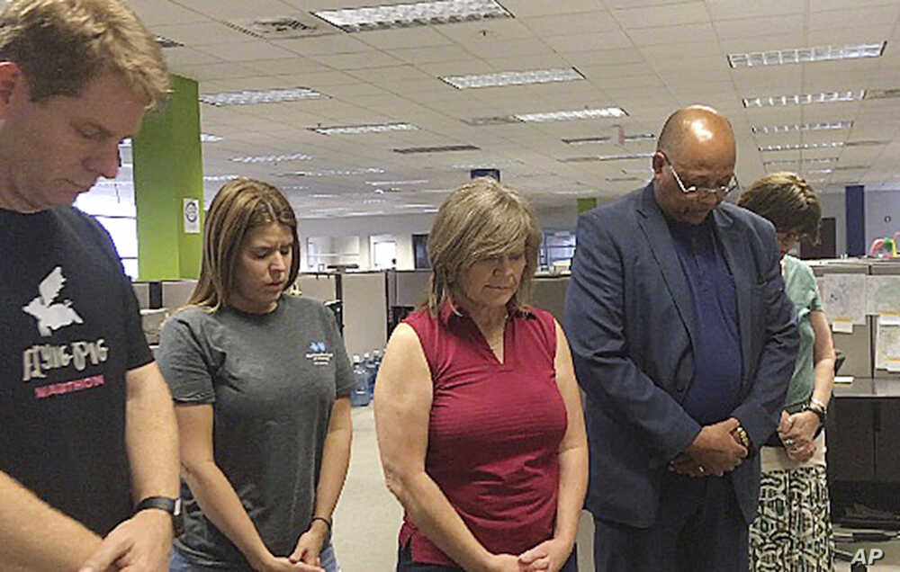 Employees in the Clarion Ledger newsroom in Jackson, Miss., observe a moment of silence, July 5, 2018, to honor five people shot to death a week earlier at the Capital Gazette in Annapolis, Md. Pictured are editorial cartoonist Marshall Ramsey, repor