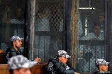 FILE - Police officers sit in the court as suspects are seen behind a fence in Cairo, Egypt, July 28, 2018.