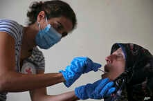 FILE - A member of the International Red Cross takes a saliva sample from a woman whose sister went missing in 1976 during the Lebanese civil war, at her home, in a southern suburb of Beirut, Lebanon, July 11, 2016.
