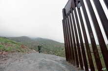 Border Patrol agent Vincent Pirro looks on near where a border wall ends that separates the cities of Tijuana, Mexico, and San Diego, Feb. 5, 2019, in San Diego.