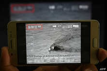A Pakistani journalist watches a video released by Pakistan's Navy that allegedly shows an Indian submarine, on a smartphone in Islamabad on March 5, 2019.