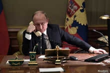 FILE - Russian President Vladimir Putin sits at a table during a telephone conversation in St. Petersburg, Russia, Dec. 15, 2018.