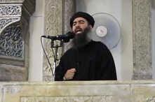 """FILE - This image from video posted in July purports to show Islamic State leader Abu Bakr al-Baghdadi delivering a sermon in Iraq; he's said to have been wounded with British national """"Jihadi John"""" in an airstrike last Saturday."""