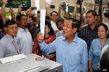 Cambodian Prime Minister Hun Se looks his ballot at a polling station in Takhmua, Kandal province, southeast of Phnom Penh, Cambodia, Sunday, July 29, 2018.