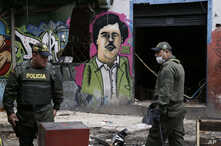 FILE - Police officers stand in front of a mural depicting the late drug kingpin Pablo Escobar, in the area known as El Bronx in downtown Bogota, Colombia, May 30, 2016. The area has been plagued by drug addicts and prostitution, including underage g