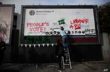 """Young members of Britain's opposition Labor Party write on a billboard why they want Jeremy Corbyn, the party leader, to back a """"People's Vote"""" second referendum on Britain's European Union membership, during a publicity stunt in Islington North, Cor"""