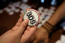 FILE - An Egyptian buys a pin with the Boycott, Divestment and Sanctions (BDS) logo during the launch of the Egyptian campaign that urges boycott, divestment and sanctions against Israel. The BDS campaign is behind the proposed boycott of Israeli uni...