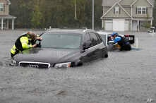 Members of the North Carolina Task Force urban search and rescue team check cars in a flooded neighborhood looking for residents who stayed behind as Florence continues to dump heavy rain in Fayetteville, N.C., Sunday, Sept. 16, 2018.