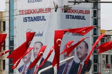 Turkish flags fly in Istanbul Taksim's square while in the background posters showing Binali Yildirim, left, the mayoral candidate for Istanbul of Turkey's President Recep Tayyip Erdogan's ruling Justice and Development Party's (AKP) and Erdogan are