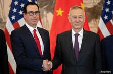 China's Vice Premier Liu He gestures next to U.S. Treasury Secretary Steven Mnuchin as they pose for a group photo at Diaoyutai State Guesthouse in Beijing, March 29, 2019.
