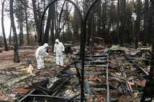 Jerry and Joyce McLean, wearing hazmat suits, look for sentimental items while sifting through the remains of their home, Dec. 5, 2018, in Paradise California.