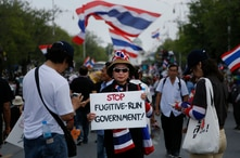 """A protester holds a placard denouncing the government outside the government house in attempts to """"shutdown"""" Bangkok, Thailand, Feb. 17, 2014."""