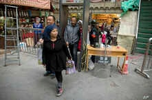 FILE - Residents past through one of the many security check points in Kashgar in western China's Xinjiang region, Nov. 4, 2017.