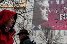People pass by a pre-election poster of Ukrainian President and presidential candidate Petro Poroshenko in central Kyiv, March 25, 2019.
