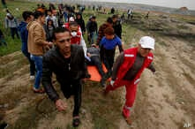 Medics and protesters evacuate a youth who was shot by Israeli troops near the Gaza Strip's border with Israel while marking first anniversary of Gaza border protests east of Gaza City, March 30, 2019.