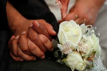 FILE - Newlyweds holds hands during a mass wedding ceremony.