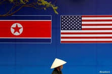 A person walks past a banner showing North Korean and U.S. flags ahead of the North Korea-U.S. summit in Hanoi, Vietnam, Feb. 25, 2019.