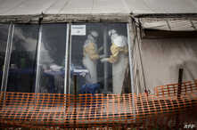 "FILE - Health workers are seen inside the ""red zone"" of an Ebola treatment center, which was attacked in the early hours of March 9, 2019 in Butembo."