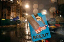 Vehicles drive past an anti-Brexit placard that is placed near the Parliament in London, Jan. 29, 2019.