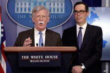 National security adviser John Bolton speaks as Treasury Secretary Steven Mnuchin listens during a press briefing at the White House, Jan. 28, 2019, in Washington.