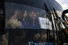 Venezuelan opposition deputies wave while traveling in a caravan of buses heading to the border with Colombia to bring in US-supplied humanitarian aid, in Caracas on Feb. 21, 2019.