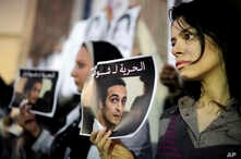 FILE - Egyptian journalists hold posters calling for the release from prison of photographer Mahmoud Abu Zeid, also known as Shawkan, in front of the Syndicate of Journalists building in Cairo, Egypt, Dec. 9, 2015.