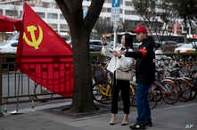 A deputized citizen gives direction to a resident near a Chinese Community Party flag on the streets of Beijing, China, Oct. 16, 2017.