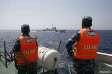 Officers of the Vietnamese Marine Guard monitor a Chinese coast guard vessel (top) on the South China Sea, about 210 km (130 miles) offshore of Vietnam, May 15, 2014.