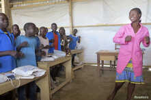 FILE - Teneng Sidonie Weteck sings and dances in class at a school for displaced Nigerian children at the Minawao camp, northern Cameroon, February 18, 2015.