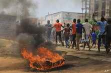 Protesters walk past a burning tyre in the Eastern Congolese town of Beni, Friday Dec. 28, 2018, as they demonstrate against the election postponed until March 2019, announced by Congo's electoral commission for Beni residents that is blamed on a dea