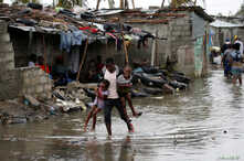 A man carries his children after Cyclone Idai at Praia Nova, in Beira, Mozambique, March 23, 2019.