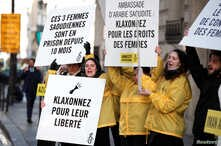 FILE - Demonstrators from Amnesty International hold placards outside the Saudi Arabian Embassy to urge Saudi authorities to release jailed women's rights activists Loujain al-Hathloul, Eman al-Nafjan and Aziza al-Yousef in Paris, France, March 8, 20