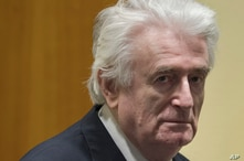 Former Bosnian Serb leader Radovan Karadzic enters the court room of the International Residual Mechanism for Criminal Tribunals in The Hague, Netherlands, Wednesday, March 20, 2019.