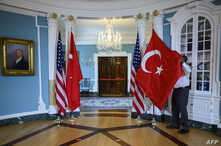 A State Department staffer adjusts a Turkish flag before a meeting between U.S. Secretary of State Mike Pompeo and Turkish Foreign Minister Mevlut Cavusoglu, at the U.S. Department of State in Washington, April 3, 2019.