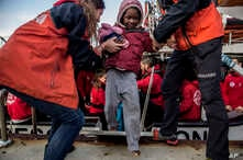 A migrant child is helped from the Spanish NGO Proactiva Open Arms rescue vessel, after being rescued Dec. 21, in the Central Mediterranean Sea, to disembark in the port of Crinavis in Algeciras, Spain, Dec. 28, 2018.