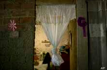 A curtain hangs in the doorway of what was the bedroom of Jhonny Godoy in La Vega slum of Caracas, Venezuela,  Feb. 19, 2019. According to his family, two days after proclaiming his opposition to President Nicolas Maduro on Twitter, special police ag
