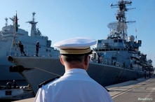 A French Navy Captain looks at the French Navy frigate Montcalm arriving at the naval base in Toulon, France, Aug. 1, 2014. French and British warships will sail the South China Sea in a display of naval strength.