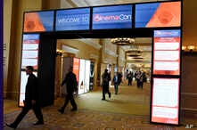 FILE - CinemaCon attendees walk through the lobby during CinemaCon 2018 in Las Vegas, the official convention of the National Association of Theatre Owners, April 26, 2018.