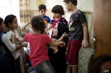 In this Aug. 19, 2018 photo, children gather around Sukaina Mohammed Ali, a top official of the local Mosul government, at an orphanage in Mosul, Iraq. Nearly 60 children are kept in two orphanages in Mosul, Iraq's second largest city.