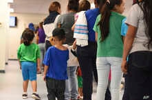 FILE - Photo provided by U.S. Immigration and Customs Enforcement shows mothers and their children standing in line at South Texas Family Residential Center in Dilley, Texas, Aug. 9, 2018.