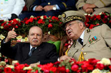 FILE - Algeria's President Abdelaziz Bouteflika gestures while talking with Army Chief of Staff Lt. Gen. Ahmed Gaed Salah during a graduation ceremony of the 40th class of the trainee army officers at a military academy in Cherchell, west of Algiers,